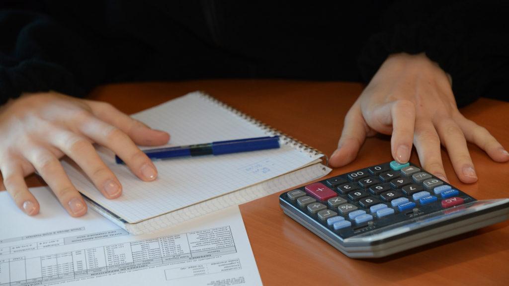 Main avec cahier et calculatrice